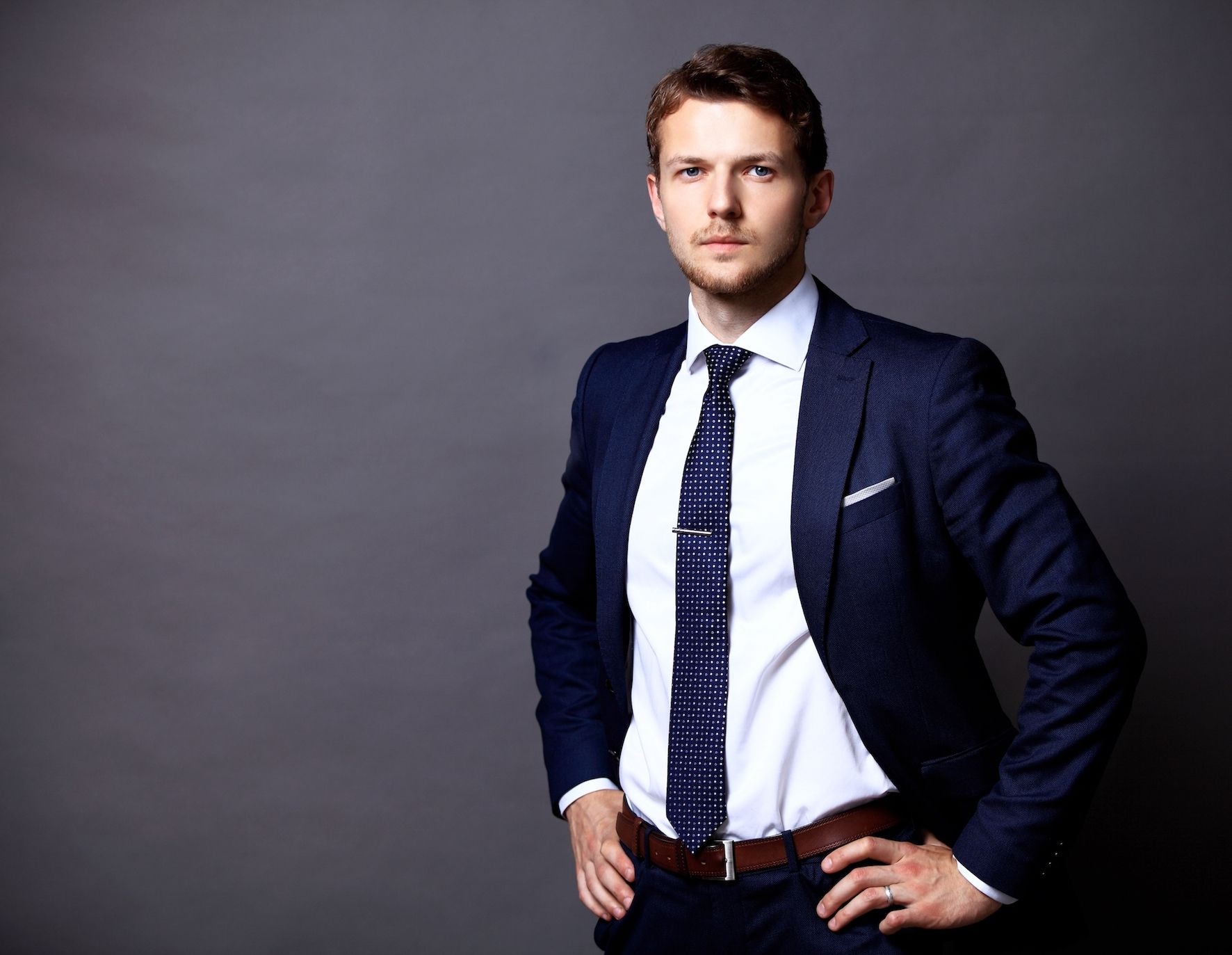 Cool young businessman standing on grey background