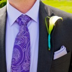 A groom and his boutonniere on his wedding day. He is wearing a suit with a single flower on the lapel of his jacket.