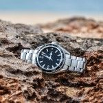 Expensive swiss wrist watch lying on a rock on the island of Molokai, Hawaii. Logo of the watch maker removed. The swiss watch making industry is world famous for its high priced luxury watches.