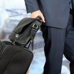 young businessman  in  a modern  stylish suit with  luggage in  the airport