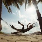 Silhouette of girl lying in hammock under palm trees on the beach. Summer, enjoyment relaxing